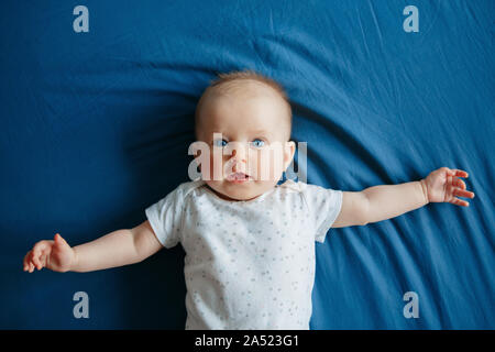 Portrait of cute adorable smiling white Caucasian baby girl boy with blue eyes four months old lying on bed in bedroom looking at camera. View above