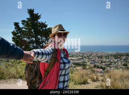 Attractive young woman tourist with a backpack on nature leads a guy by the hand. follow me - Stock Photo