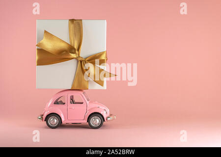 Little retro toy model car with present gift box on pastel pink background. Christmas, birthday, valentines day, delivery concept - Stock Photo