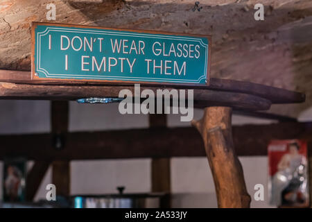 Funny inscription above the bar on a metal sign made of sheet painted green. - Stock Photo