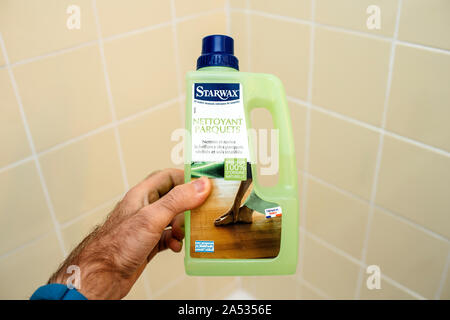 Paris, France - Dec 1, 2017: Male hand holding against bathroom tiles bootle of Starwax wooden floor cleaning solution from 100 percent bio organic ingredients - Stock Photo