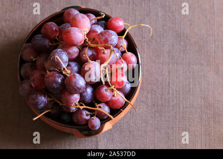 Ripe red grapes in a bowl isolated on brown background. Top view - Stock Photo