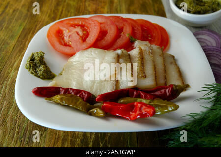 Appetizing snack. Sliced smoked pork lard, tomatoes, pickled chili peppers and pesto sauce lie on brown wooden surface. Close-up. - Stock Photo