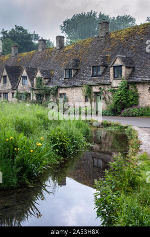 Traditional cotswold stone cottages built of distinctive yellow limestone in the world famous Arlington Row, Bibury, Gloucestershire, England - Stock Photo
