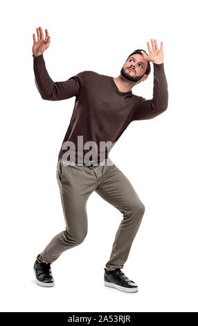 A bearded man in casual garb stands cowering under something dangerous above him. - Stock Photo