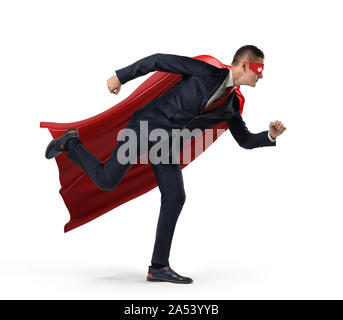 A businessman in a hero red cape and a mask in side view ready to run with one leg already in air on white background. - Stock Photo