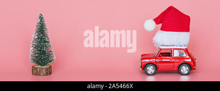 Changxing, China - October 15, 2019: Red toy car with a santa hat, next christmas tree on pink paper background. Winter delivery, xmas, happy new year - Stock Photo