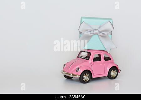 Changxing, China - October 15, 2019: Pink retro toy car delivering gift box on roof on white background. Valentine day February 14, International - Stock Photo