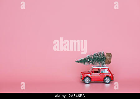 Changxing, China - October 15, 2019: Red toy car with a christmas tree on the roof on pink paper background. Winter delivery, xmas, happy new year - Stock Photo