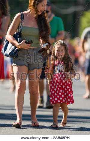 Woman holding the hand of a young girl walking down Baldwin Avenue during the second leg of the stick horse race held before the start of 54th annual - Stock Photo