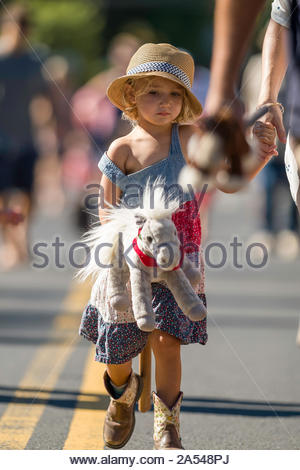 Woman holding the hand of a young girl walking down Baldwin Avenue during the second leg of the stick horse race - Stock Photo