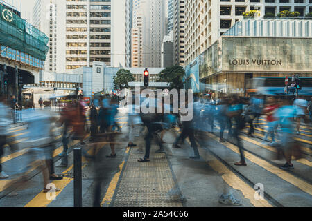 People crossing on the busy street of Central District in Hong Kong. People Walking on Zebra Crossing in Hong Kong. - Stock Photo