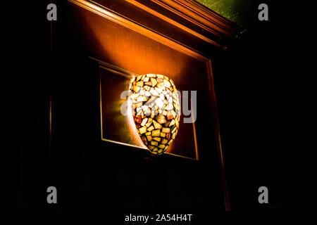 Ceiling light illuminates a dark bar, in New York City - Stock Photo