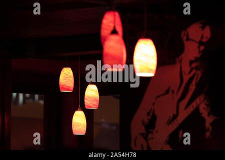 Ceiling lights illuminate a dark bar, in New York City - Stock Photo