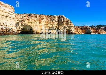 Turquoise sea waters and the sandstone cliffs of Praia da Marinha seen from a boat, Lagoa, Algarve, Portugal - Stock Photo