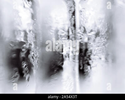 Abstract blurry wet misty glass monotone white and gray colour background with high contrast light - Stock Photo
