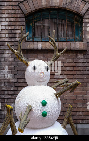 cute plastic snowman display in front of brick wall - Stock Photo