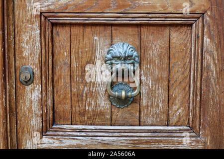 Lion door knocker on a wooden door - Stock Photo