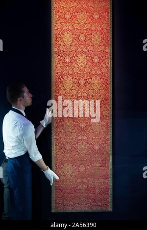 A staff member adjusts a rare Ottoman silk and metal-thread brocade panel, made in Turkey in the 17th century (est. £60,000-£80,000), during the preview of Middle Eastern Art Week at Sotheby's in London, ahead of their sale by auction on 22 and 23 October. PA Photo. Picture date: Friday October 18, 2019. Highlights of the sale will include a sumptuous leaf from the mythic 9th/10th century blue & gold Qu'ran, a dynamic painting of a great Indian epic wedding procession, jewellery including a talismanic Mughal emerald crystal weighing 363.9 carats, and paintings and sculpture by pioneering artis - Stock Photo