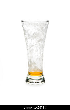 Almost empty pilsner beer glass isolated against white background. - Stock Photo