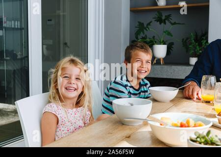 Children having lunch with father at home - Stock Photo