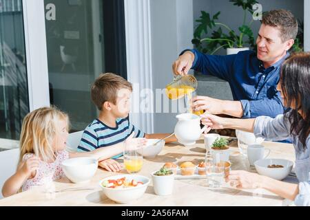 Parents having lunch with children at home - Stock Photo