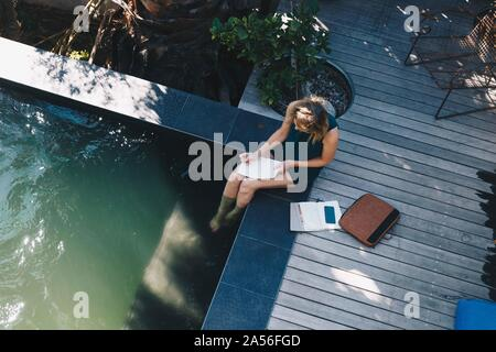 Businesswoman working on edge of swimming pool with legs in water - Stock Photo