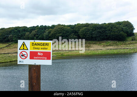 Danger deep water and no swimming sign next to a reservoir - Stock Photo