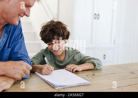 Father helping son with homework at home - Stock Photo
