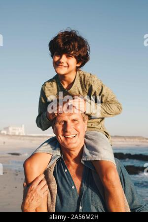 Father giving son piggyback ride on beach - Stock Photo