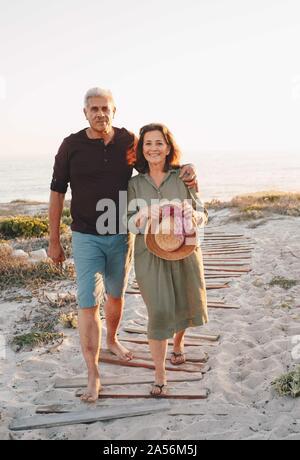 Senior couple taking walk on beach - Stock Photo
