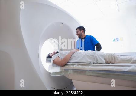 Young male radiographer operating CT scanner in radiology department - Stock Photo
