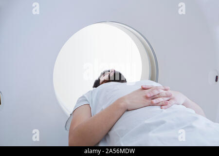 Young male patient having a CT scan in radiology department - Stock Photo