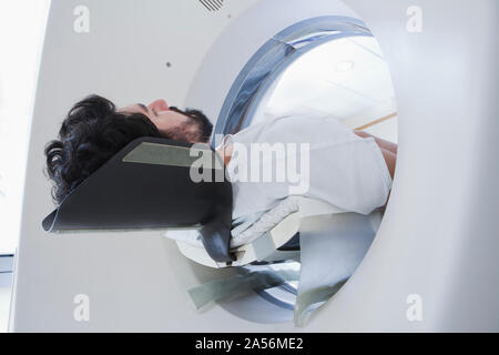 Young male patient having a CT scan in radiology department, low angle view