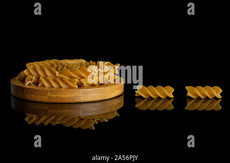 Lot of whole dry brown wholegrain fusilli on bamboo coaster isolated on black glass - Stock Photo