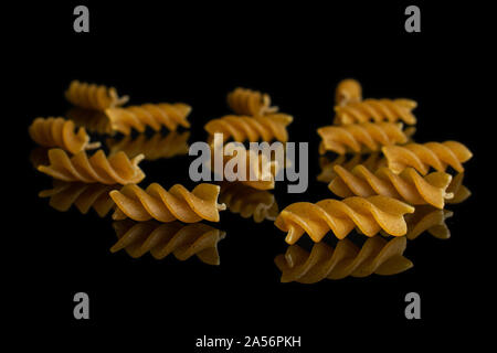 Lot of whole dry brown wholegrain fusilli isolated on black glass - Stock Photo
