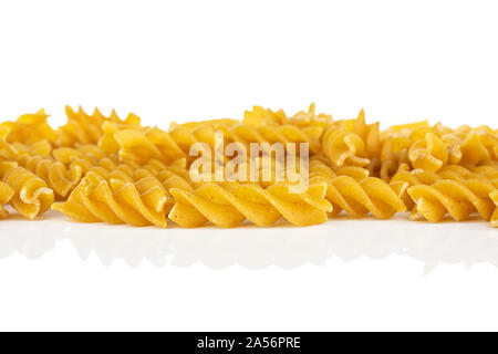 Lot of whole dry brown wholegrain fusilli isolated on white background - Stock Photo