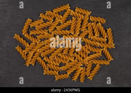 Lot of whole dry brown wholegrain fusilli flatlay on grey stone - Stock Photo