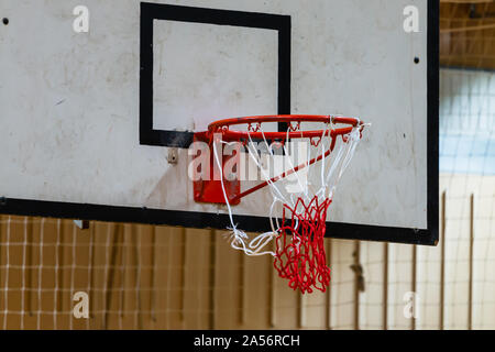 Used basketball backboard, hoop, net inside of basketball court, Left side view, close up - Stock Photo