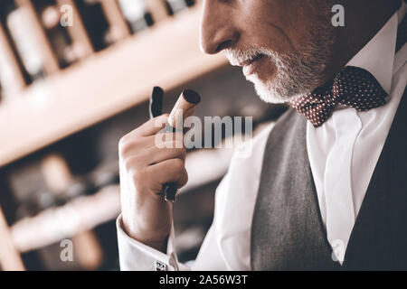Sommelier Concept. Senior man standing with corkscrew smelling cork close-up - Stock Photo