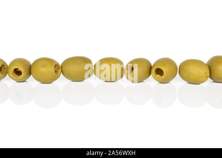 Group of nine whole marinated green olive in row isolated on white background - Stock Photo
