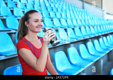 Beautiful sportswoman drinking water after work out at the stadium. - Stock Photo