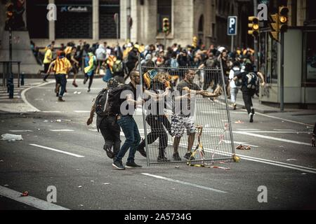 Barcelona, Catalonia, Spain. 18th Oct, 2019. Barcelona, Spain. 18 Oktober, 2019: .Striking Catalan pro-independence activists try to cover with a construction fence before they clash with Spanish National police riot officers during a protest against the Supreme Court's verdict against 9 of 12 Catalan leaders for sedition, misuse of public funds and desobedience in relation with a banned referendum on secession and an independence vote at the Catalan Parliament in October 2017. (Credit Image: © Matthias OesterleZUMA Wire) - Stock Photo