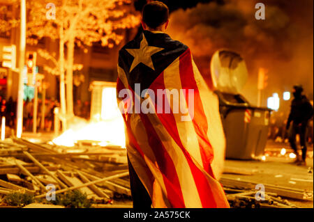 Barcelona, Spain - 18 october 2019: catalan activist with catalan flag at night with fire and destruction in background during clashes with police - Stock Photo