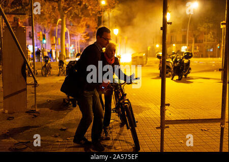 Barcelona, Spain - 18 october 2019: scared old woman walk past riots and fire between police and catalan independetists - Stock Photo