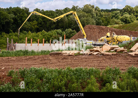 construction site; heavy equipment; pouring concrete foundation; new building; brown dirt; trees; green wild ground cover; trees, boulders, Pennsylvan - Stock Photo