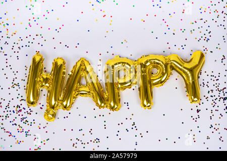 Happy letters of frustrated golden balloons isolated with colorful confetti on white background. Congratulations. - Stock Photo