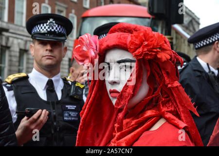 London, UK. 18th Oct, 2019. Activists sprayed red hands on government departments on Friday in London, as they continue their protest to urge the government to take action on the climate emergency. Nearly 1,800 Extinction Rebellion protesters have been arrested as of 2pm today, police said, as the group continued its protests in defiance of a police ban. (Photo by Laura Chiesa/Pacific Press) Credit: Pacific Press Agency/Alamy Live News