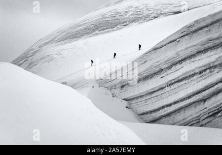 Figures of climbers pass a large crevasse on the Allalinhorn high in the Swiss Alps - Stock Photo