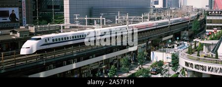 300 series Shinkansen train arriving at a railroad station, Tokyo Prefecture, Kanto Region, Honshu, Japan - Stock Photo
